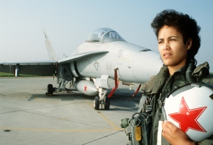 Lt. J.G. Christina Green, a naval flight officer, poses for a photograph in front of an F/A-18A Hornet aircraft. Green is a member of Tactical Electronic Warfare Squadron 34 (VAQ-34).